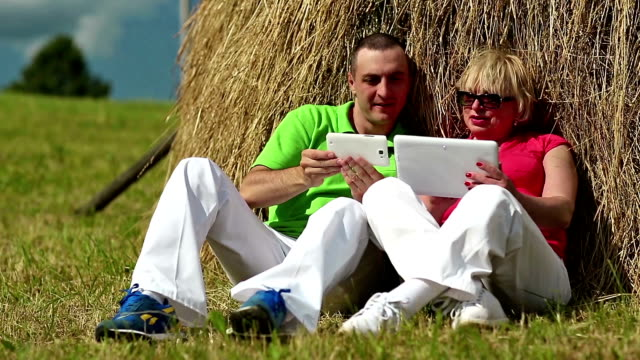 man with white smartphone and woman with white tablet pc sits near a haystack - son stock videos and b-roll footage