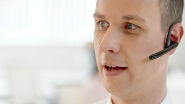 TU homem com fone de ouvido sem fio, para o cliente falando - vídeo
