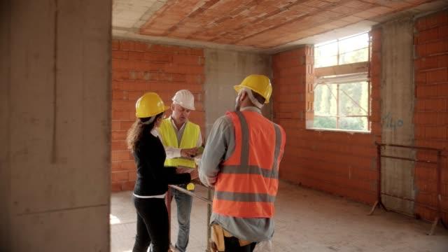 vidéos et rushes de homme, femme et réunion de travailleur manuel en chantier - hlm