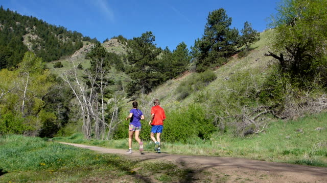 Man woman couple morning running Bear Creek Trail Colorado Rocky Mountains video