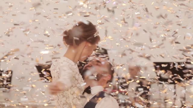 man woman happy couple dance embracing under shining golden light confetti falling from above. groom holds bride in hands twirling her celebrating festive mood music band playing live at background - matrimonio video stock e b–roll
