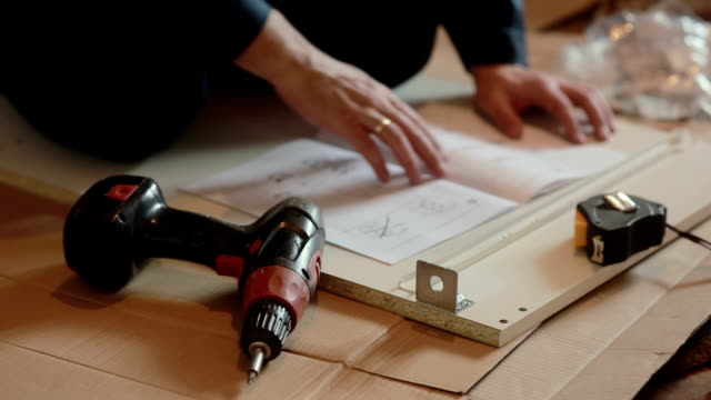 man worker assembles furniture using instruction video