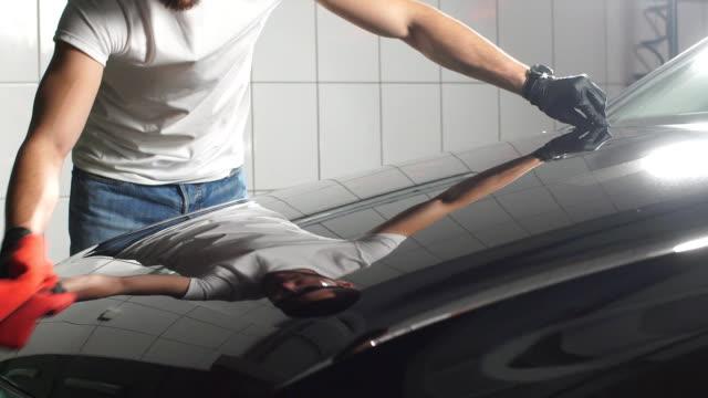 mann-arbeiter polieren auto auf einer autowaschanlage - wachs epilation stock-videos und b-roll-filmmaterial