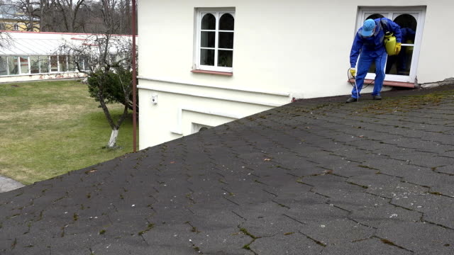 man worker spray destroy the moss growing on the home roof. FullHD video