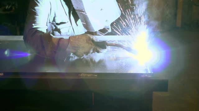 Man working as manual worker and welder in steel factory video