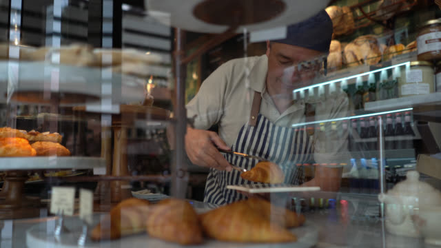 Man working at a bakery grabbing a croissant with tongs