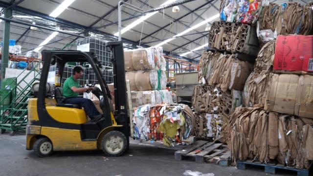 Mann arbeitet in einer recycling Fabrik auf einem LKW Gabelstapler recycelt Bulks von einem Ort zum anderen bewegen – Video