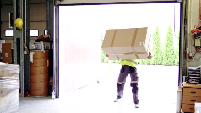 man working at a warehouse. carrying heavy boxes - тяжёлый стоковые видео и кадры b-roll