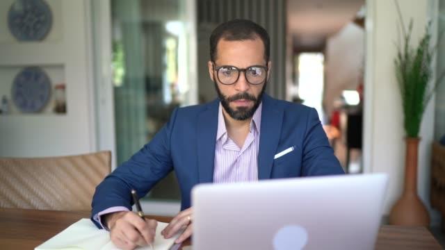 vídeos y material grabado en eventos de stock de hombre que trabaja en casa - financial planning