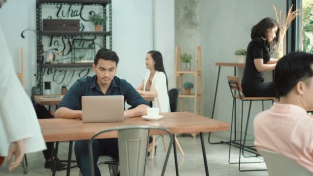 Man working at laptop, drinking cappuccino at table in cafe