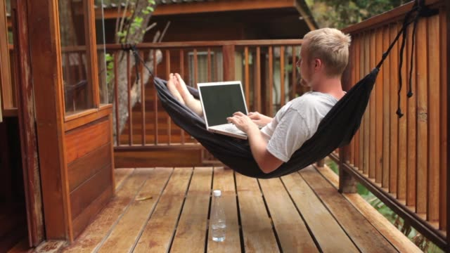 man working behind a laptop in a hammock on a terrace in the jungle - amaca video stock e b–roll