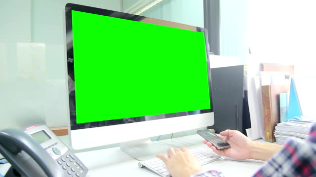Man working both Smartphone and Computer with green screen video