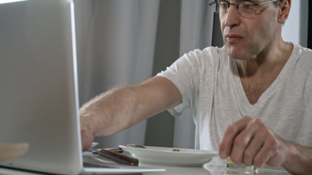 vídeos de stock e filmes b-roll de man working from home and having breakfast - remote work