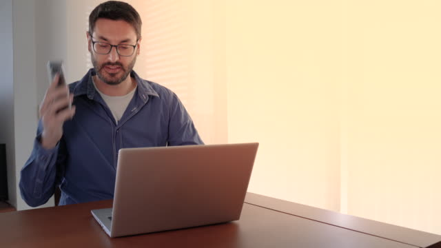 Man working from home and picking up the phone
