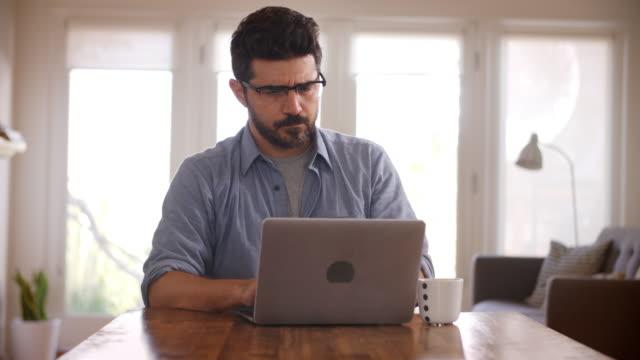 man som arbetar från hem med laptop på matbord - working from home bildbanksvideor och videomaterial från bakom kulisserna