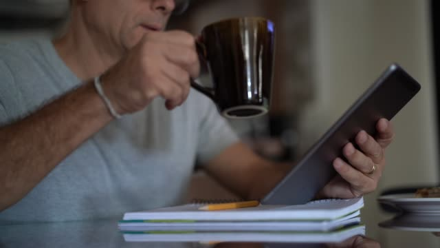 Man working from home while taking breakfast video