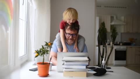 vidéos et rushes de homme travaillant de la maison avec l'ordinateur portatif pendant la quarantaine. bureau à domicile et la parentalité en même temps. - parents