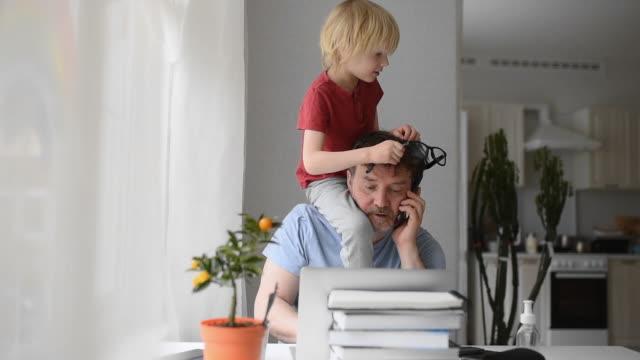 검역 중 노트북으로 집에서 일하는 남자. 홈 오피스와 동시에 부모. 활동적인 자녀를 가진 지친 부모. - 짜증 스톡 비디오 및 b-롤 화면