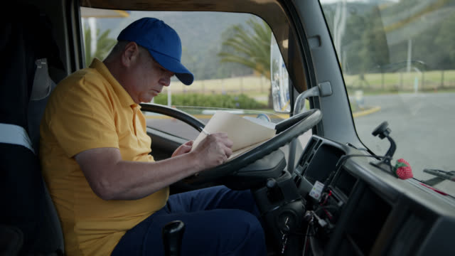 Man working in a truck filling in a form before delivering a product to customer Man working in a truck filling in a form before delivering a product to customer - business concepts clipboard stock videos & royalty-free footage