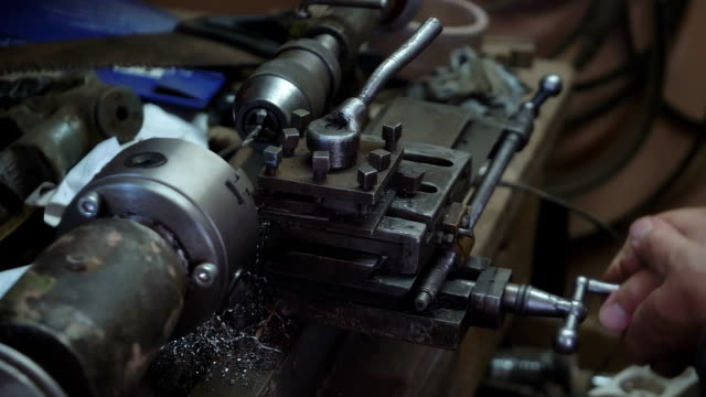 Man working in a workshop on lathe in slow motion 180fps video