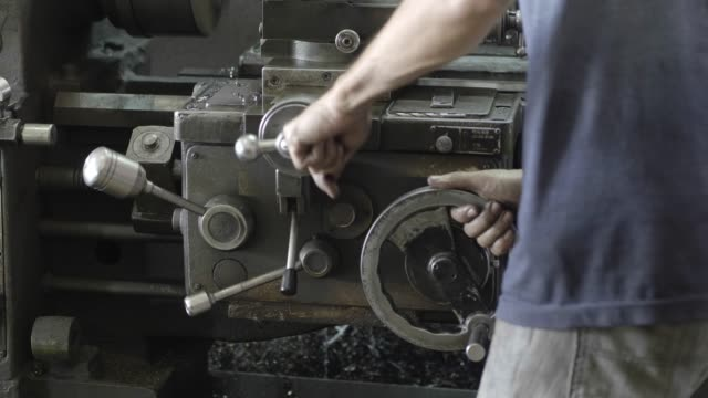 Man working in a workshop on lathe machine in the industrial factory. slow motion Man working in a workshop on lathe machine in the industrial factory. slow motion workbench stock videos & royalty-free footage
