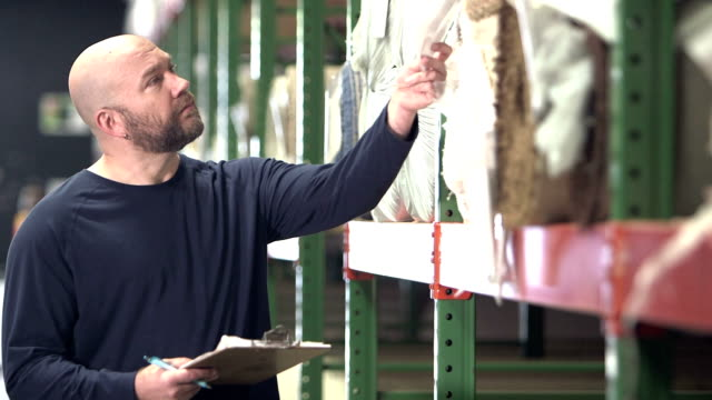 Man working in carpet warehouse taking inventory video