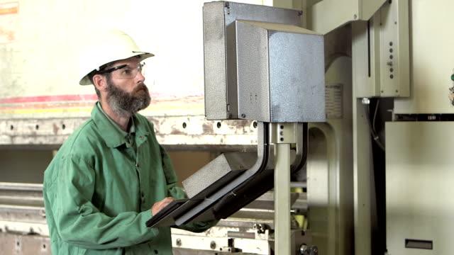 man working in factory setting controls on machinery - warsztat filmów i materiałów b-roll