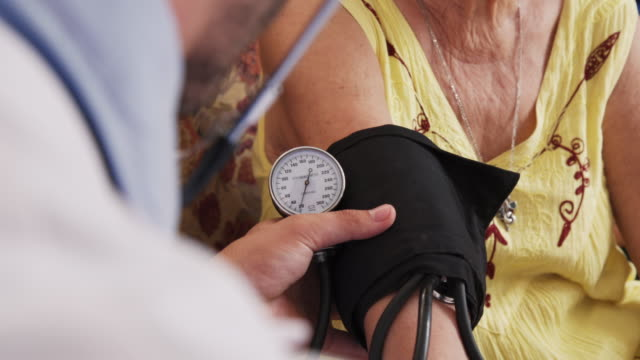 Man Working In Hospice And Measuring Blood Pressure Of Woman – Video