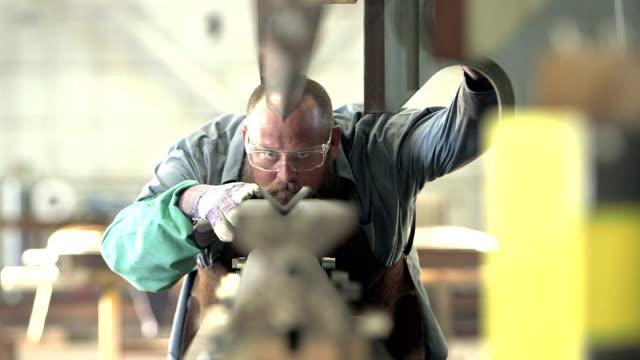 금속 제작 상점에서 일 하는 남자 - 결심 스톡 비디오 및 b-롤 화면