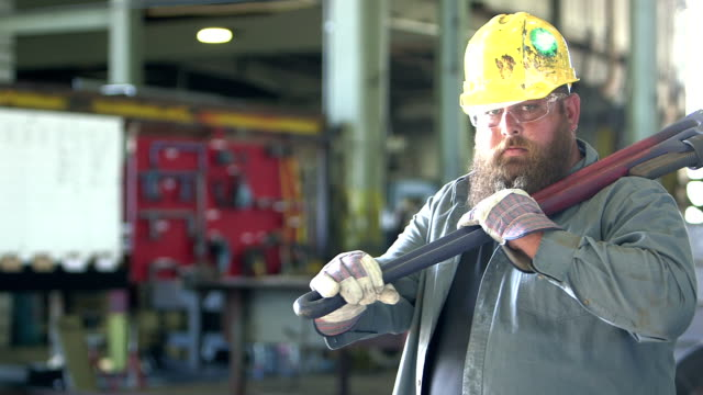 Man working in repair shop carrying giant wrench A heavyset man with a beard in his 30s, working in a repair shot, wearing a hard hat and safety glasses. He puts a large work tool over his shoulder and stares at the camera with a tough expression. macho stock videos & royalty-free footage