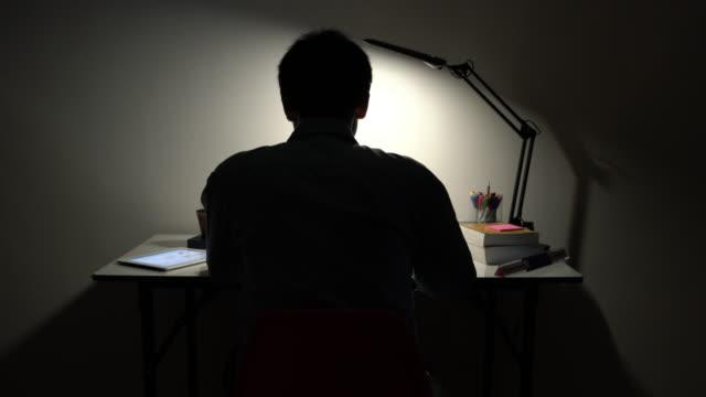 stockvideo's en b-roll-footage met man aan het werk laat in de nacht - overwerken