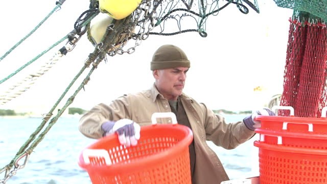 Man working on commercial fishing boat stacking baskets