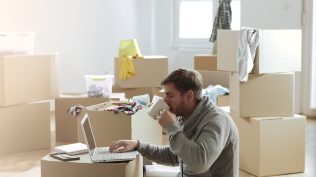 vídeos de stock, filmes e b-roll de homem trabalhando no laptop e beber café em seu novo apartamento cheio de caixas descompactadas - college people laptop