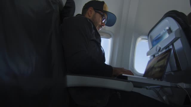 Man working on laptop while traveling on airplane video