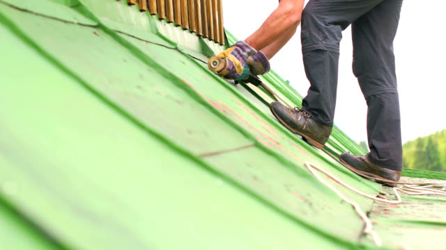 Man Working on the Roof, Sandering Paint video
