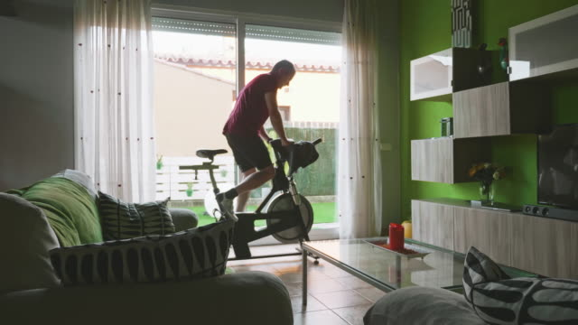 man working out on exercise bike at home - sprzęt do ćwiczeń filmów i materiałów b-roll
