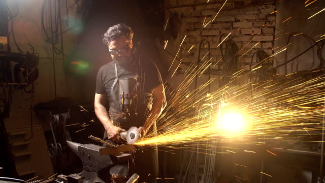 Man working the angle grinder in the workshop. Blacksmith working with metal. a man in working clothes Blacksmith forges on the anvil. brutal man working at the forge with metal anvil stock videos & royalty-free footage