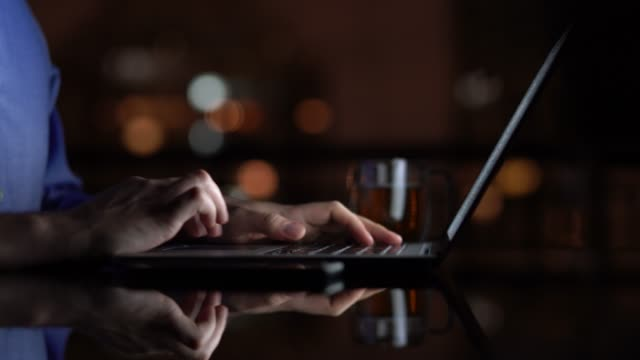 Man working / using laptop at home at night