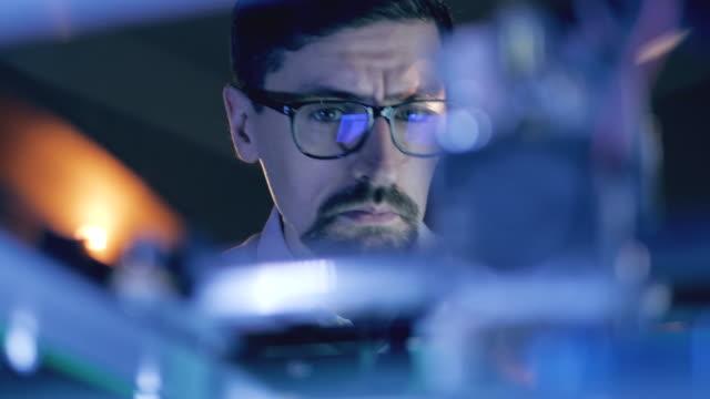 uomo che lavora con una stampante 3d presso il laboratorio di stampa 3d. lo specialista maschile in occhiali osserva un meccanismo di lavoro - industria elettronica video stock e b–roll