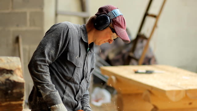 Man working with a chainsaw. Wood shavings are flying saw his face. Close up video
