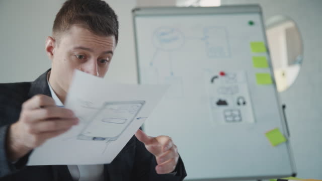 Man working with sketch page for website in office