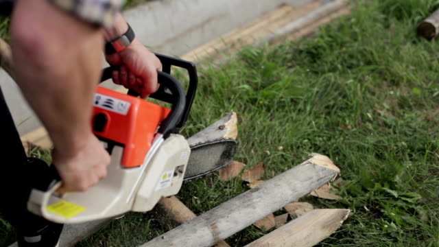 man works chainsaw close-up video