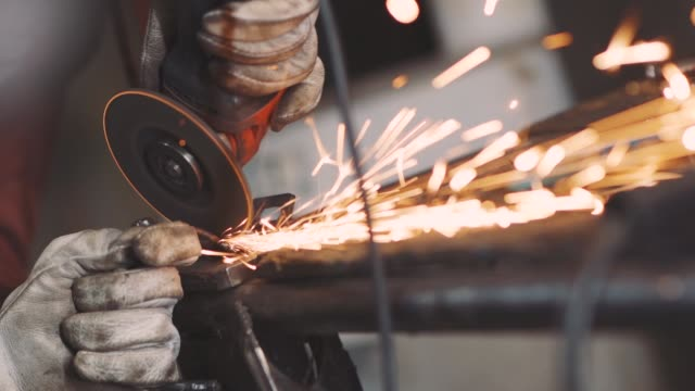 man works circular saw. sparks fly from hot metal. man hard worked over the steel. close-up slow motion shot in garage - rettificatrice video stock e b–roll