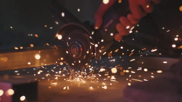 Man works circular saw. Sparks fly from hot metal. Man hard worked over the steel. Close-up slow motion shot in garage