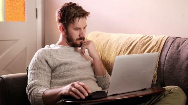 男は彼のソファから働く - 三脚 - あごヒゲ点の映像素材/bロール