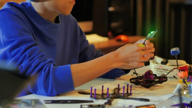 A man works on a fully functional programable Robot for robotics club project.Creative designer testing robotics prototype in workshop.Innovation,Science concept