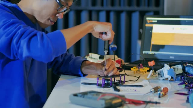 A man works on a fully functional programable Robot for robotics club project.Creative designer testing robotics prototype in workshop.Innovation,Science concept.Industry 4.0