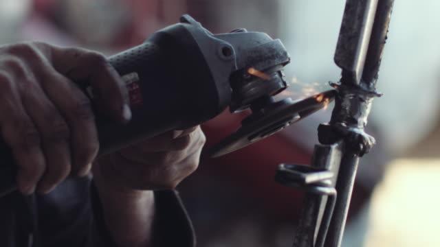 człowiek pracuje z szlifierką w swoim garażu - stock video - narzędzie z napędem elektrycznym filmów i materiałów b-roll
