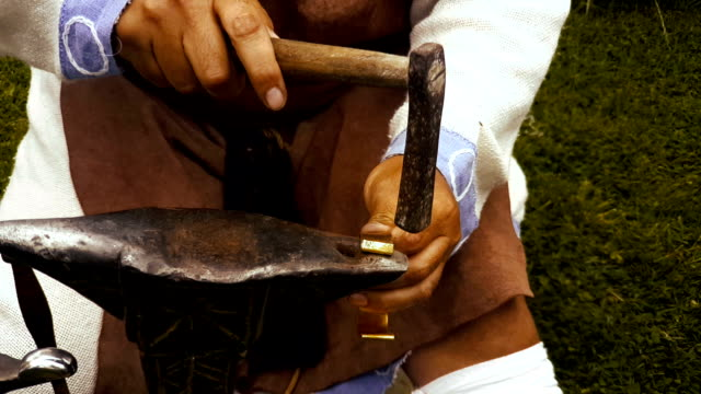 Man works with hammer and anvil coppersmith bracelet historical reconstruction video