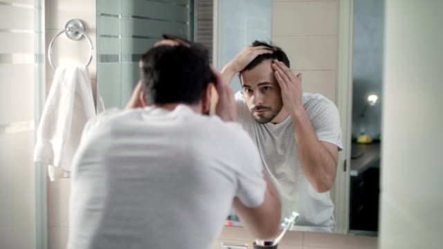 Man Worried For Alopecia Checking Hair For Loss Latino person with beard grooming in bathroom at home for morning routine and body care. White metrosexual man worried for hair loss and looking at mirror his receding hairline. hairstyle stock videos & royalty-free footage